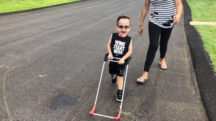 Jaxon age 2, has tunnel vision, he strides down the street with confidence wearing his pediatric belt cane.